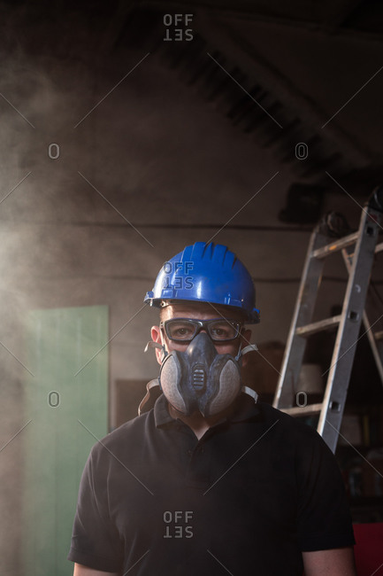 Low angle front view of male worker in hardhat and respirator during accident in smoked workshop