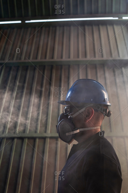 Low angle side view of male worker in hardhat and respirator during accident in smoked workshop