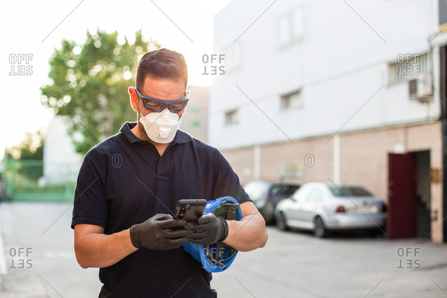 Serious male mechanic in protective glasses and respirator with gloves messaging on mobile phone while standing on street and having break during work in workshop