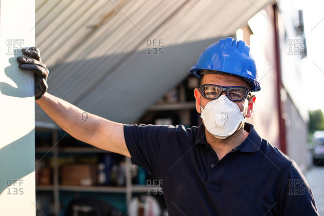 Adult male mechanic in protective glasses and respirator with blue hardhat looking at camera while standing near workshop building on street