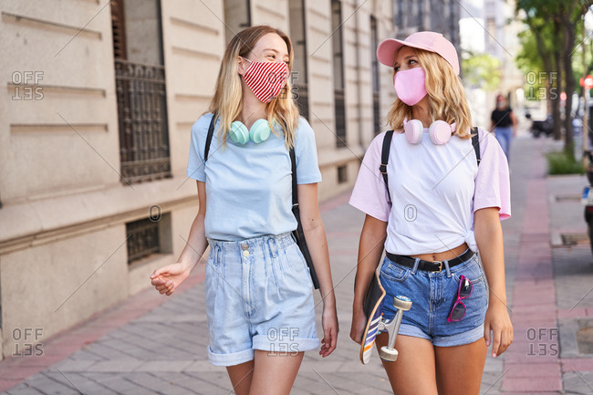 Cheerful teen female friends in trendy outfits and textile protective masks talking and laughing while standing together on city street in summer day during coronavirus pandemic