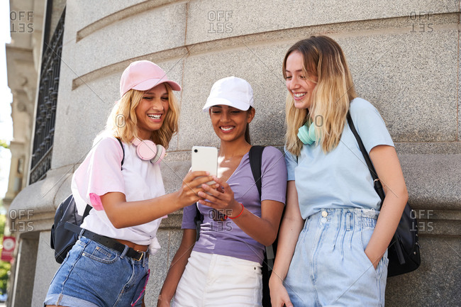 Cheerful young multiracial girlfriends in casual outfits using smartphone while standing together near stone building in city in summer day