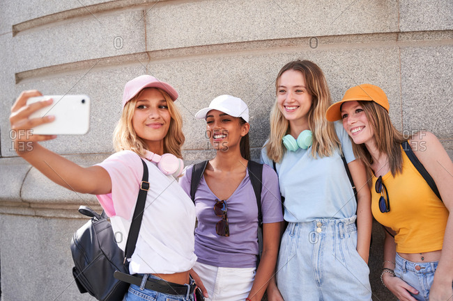 Cheerful young multiracial girlfriends in casual outfits taking selfie with smartphone while standing together near stone building in city in summer day