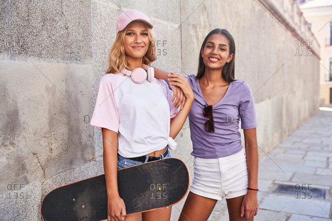 Positive multiracial female teenagers in trendy casual wear with skateboard looking at camera while standing near concrete wall on urban street in summer day