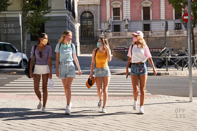 Full body cheerful multiethnic millennial girlfriends in casual outfits and protective masks for coronavirus prevention strolling on urban street in summer day