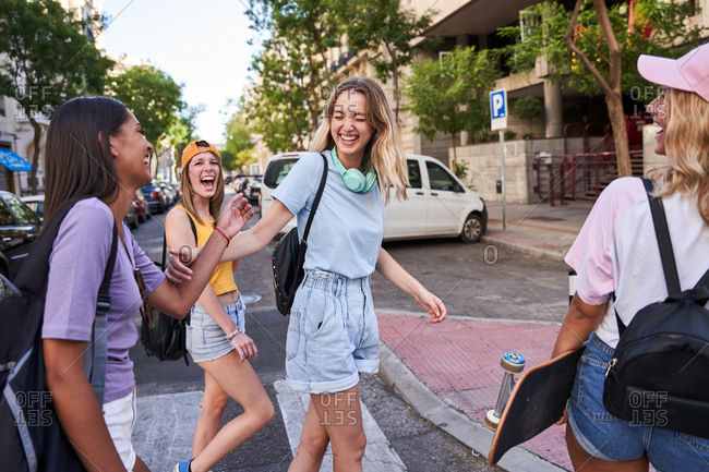 Group of cheerful multiracial teen girls in casual clothes with headphones and skateboard having fun and chatting happily while walking together on city street in summertime