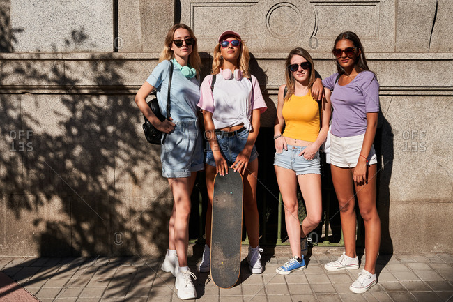 Full body of cheerful young multiracial girlfriends in casual outfits and sunglasses with skateboard looking at camera while standing together near stone building in city in summer day