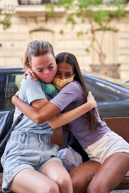 Diverse teen female friends in protective masks sitting on bench and embracing each other while spending summer day together in city