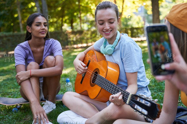 Cheerful multiracial female teenagers playing guitar and taking photo on mobile phone while sitting on green lawn in park and enjoying summer day together