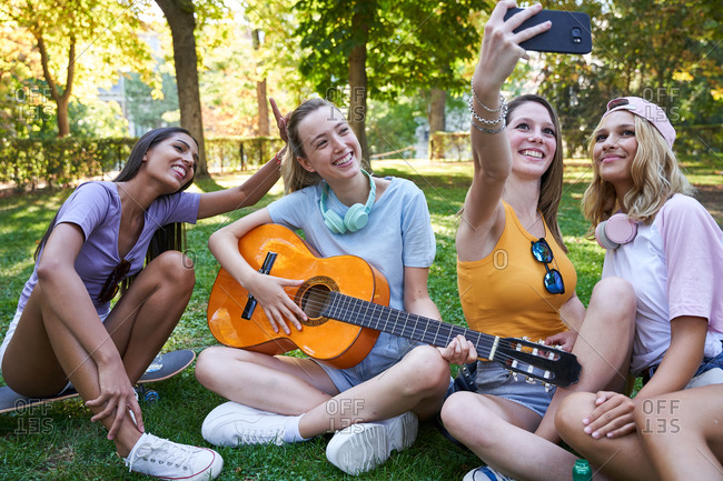 Cheerful multiracial female teenagers playing guitar and taking selfie on mobile phone while sitting on green lawn in park and enjoying summer day together