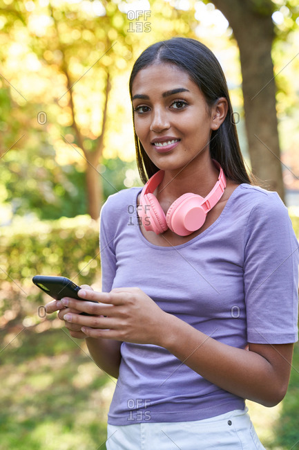 Positive ethnic female adolescent in casual outfit with headphones on neck messaging on mobile phone and looking at camera while standing in green park in summer day