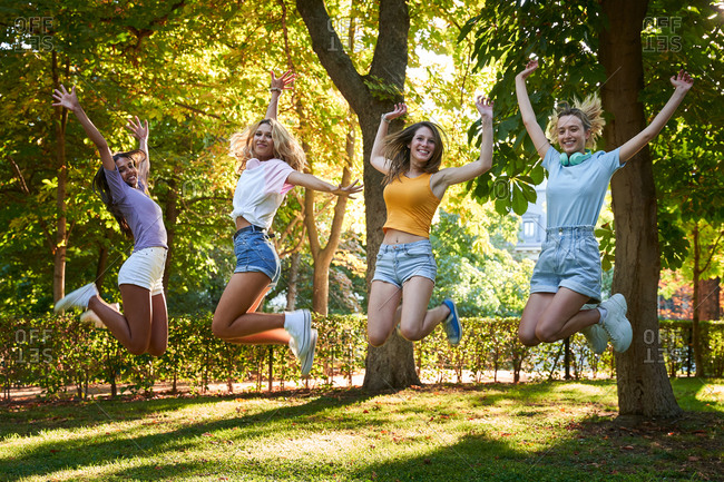 Full length optimistic active teenage female friends jumping high with arms raised while having fun together in summer park
