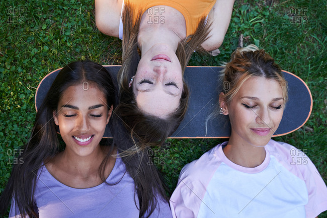 Top view of group of multiracial teen female students lying on green grass with heads on skateboard while chilling together in summer park