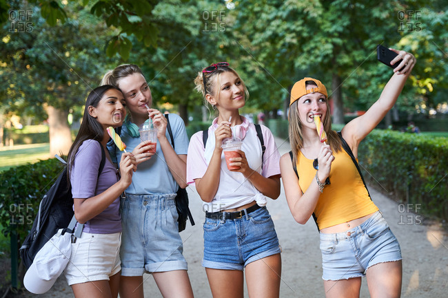 Group of cheerful diverse hipster girlfriends taking selfie on smartphone while enjoying takeaway cold beverages and fruit ice cream in summer park