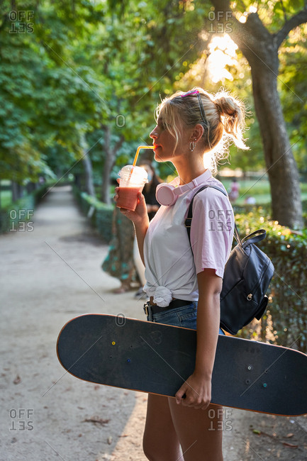 Side view of hipster teen female skater carrying skateboard and enjoying cold milkshake while resting in park in summer day