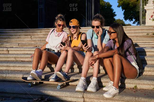 Cheerful young trendy multiracial girlfriends in sunglasses browsing mobile phones while resting together on stone stairs in sunny summer day in city park