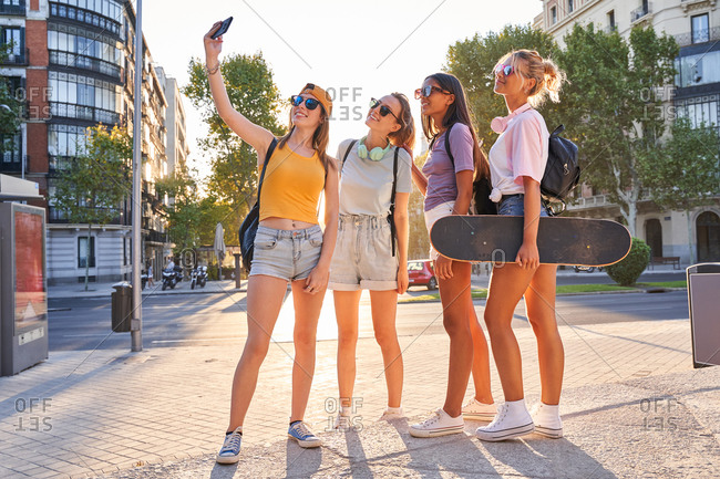 Full body of cheerful trendy young multiracial girlfriends in sunglasses with backpacks and skateboard taking selfie on mobile phone while gathering together on urban square in summer day