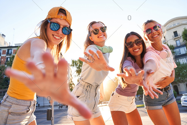 Group of modern millennial female friends in trendy outfits and sunglasses outstretching arms and looking at camera while enjoying summertime in city
