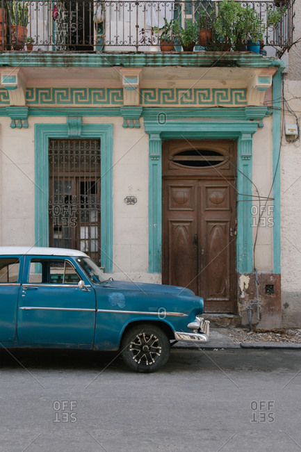 August 5, 2019: Old fashioned blue automobile parked near shabby aged building on urban street in Cuba