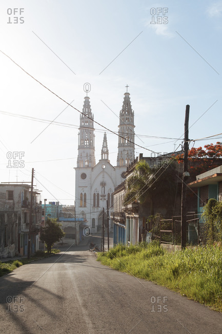 August 6, 2019: Colonial style church with steeples located on narrow street amidst small houses in suburban district in Cuba