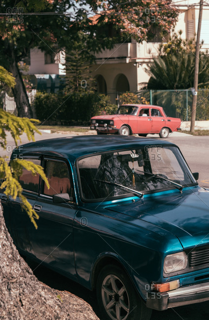 August 6, 2019: Blue retro automobile parked on narrow empty asphalt road on street of town in Cuba