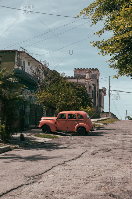August 6, 2019: Exterior of typical old residential building with car parked on roadside near uneven damaged road in urban area in Cuba