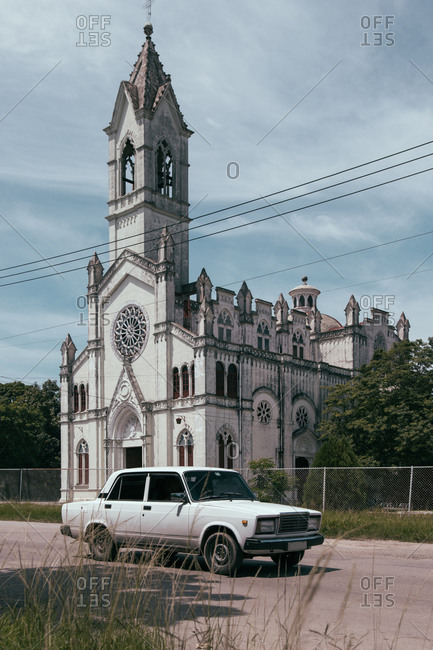 August 6, 2019: Old fashioned white vintage automobile parked near beautiful building of aged cathedral with steeple on street of Cuba