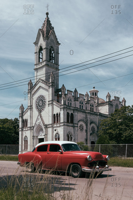 August 6, 2019: Old fashioned red vintage automobile parked near beautiful building of aged cathedral with steeple on street of Cuba