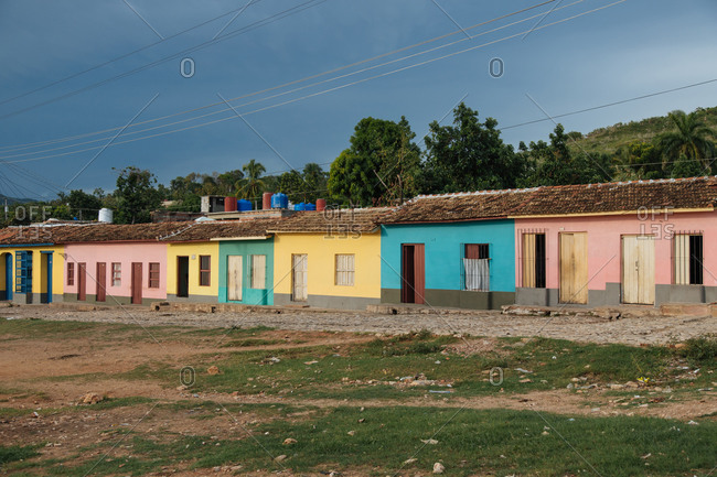 Exterior of typical aged multicolored residential cottage houses built in row near green trees on street of Cuba