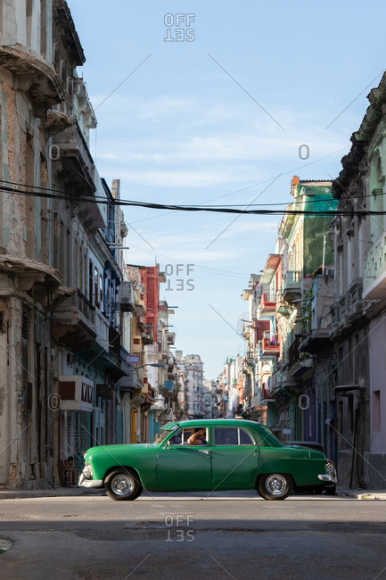 August 12, 2019: Old fashioned green automobile on a road near shabby aged buildings on urban street in Cuba