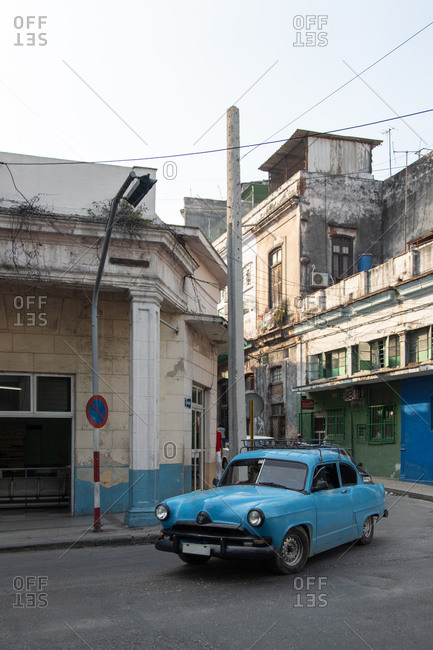 August 13, 2019: Old fashioned blue automobile parked near shabby aged building on urban street in Cuba