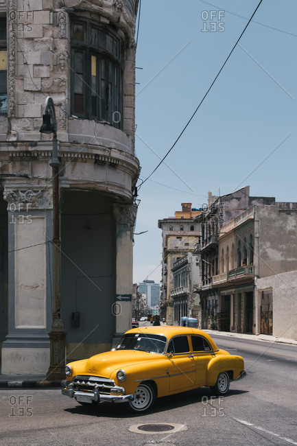 August 13, 2019: Old fashioned yellow automobile parked near shabby aged building on urban street in Cuba