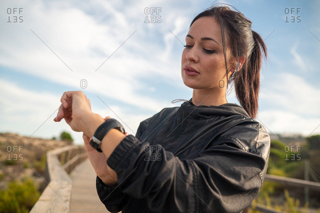 Active young brunette in black sports outfit standing on wooden pathway and checking data on fitness tracker after training in nature