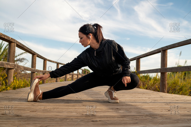 Full body of determined sportive fit female in black activewear doing stretching exercise while warming up before running on wooden walkway in nature