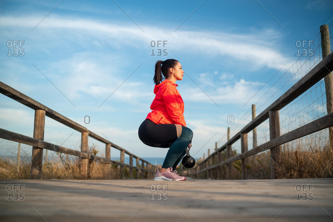 Ground level side view of fit female athlete in sportswear doing squats with kettlebell during training on wooden promenade