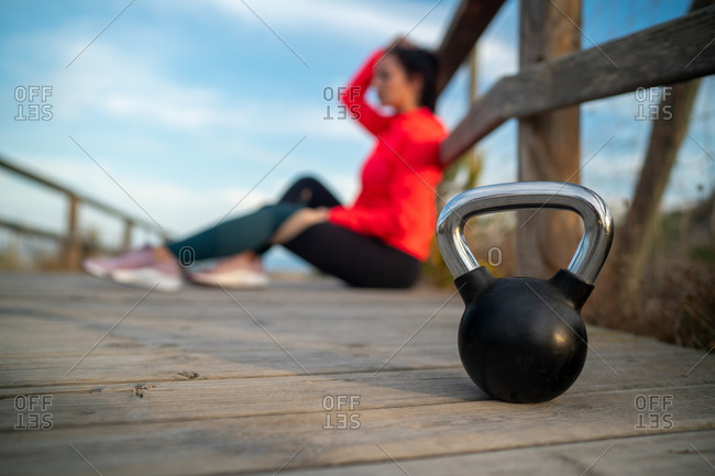 Heavy metal kettlebell placed on wooden promenade on background of blurred unrecognizable sportswoman