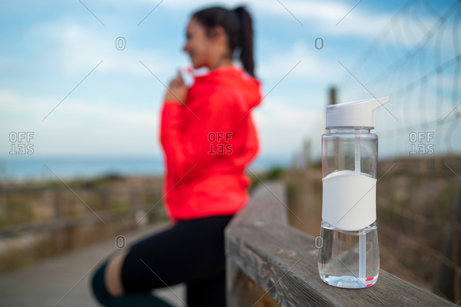 Plastic bottle with fresh water placed on wooden promenade on background of blurred female athlete