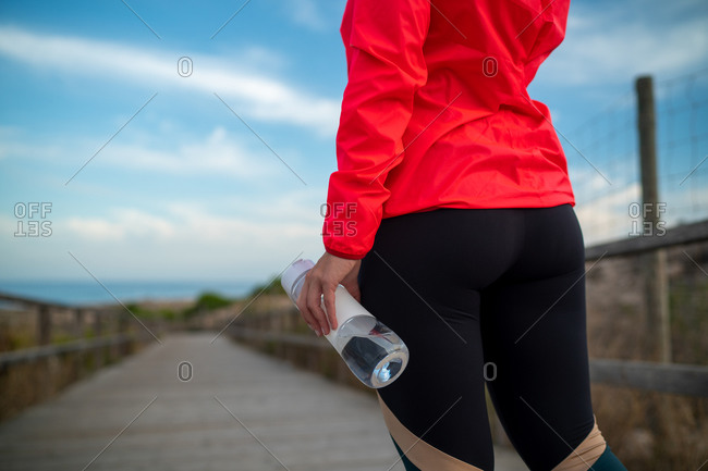 Cropped unrecognizable female athlete holding plastic bottle with fresh water standing on wooden promenade