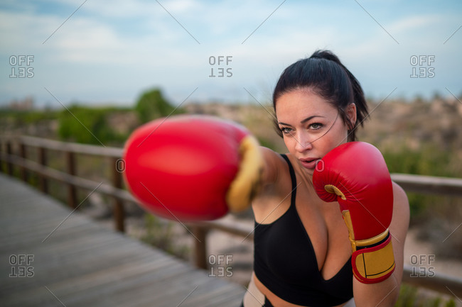 Enduring female in boxing gloves training punches during active workout on promenade in nature