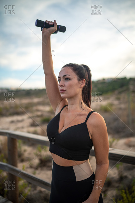 Focused athletic female in sportswear standing on embankment and training with dumbbell while looking away