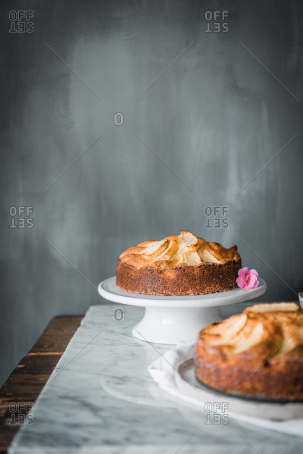 Composition with whole round delectable homemade apple cakes on plates placed on table with bowl with sweet syrup and cooking brush