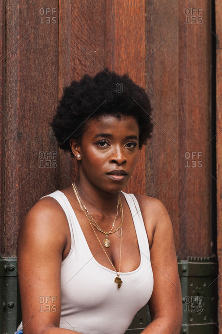Young unhappy African American female with afro hair standing against wooden wall and thoughtfully looking at camera