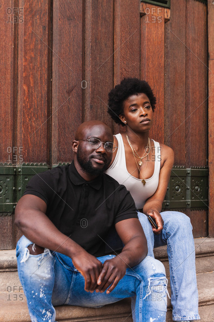 Serious young African American female and boyfriend sitting together against wooden wall looking away