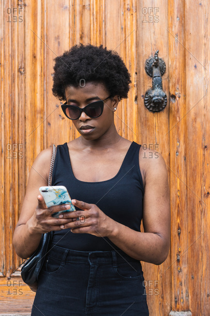 Young African American female wearing black top with decollete texting on smartphone