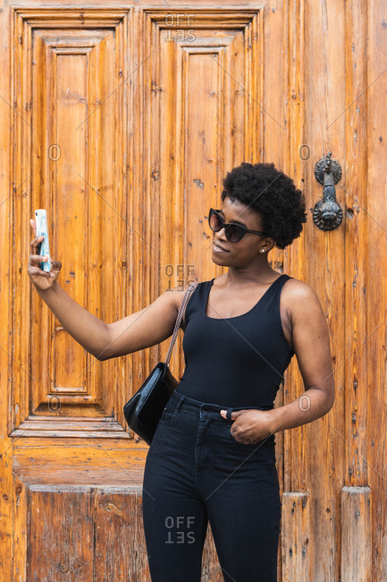 Confident African American female taking self photo on mobile phone while standing against wooden door with hand in pocket