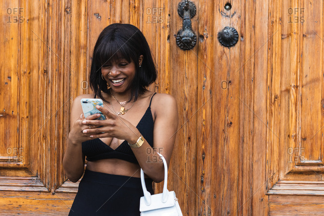 Smiling young African American female wearing black top with decollete texting on smartphone
