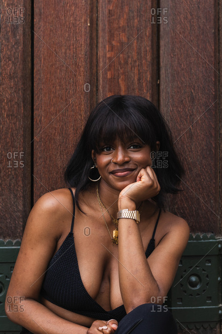 Delighted African American female standing against wooden wall looking at camera