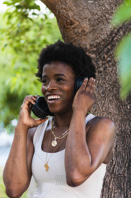 Cheerful African American female enjoying music in wireless headphones while standing near tree