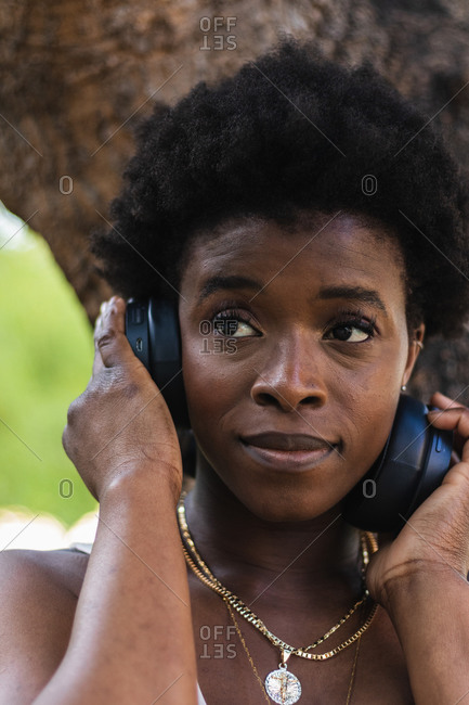 Happy African American female enjoying music in wireless headphones while standing near tree
