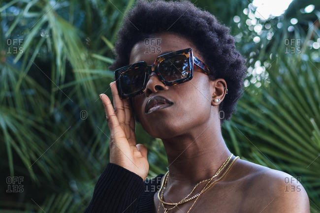 Low angle of serious African American female with Afro hairstyle in trendy glasses against palms